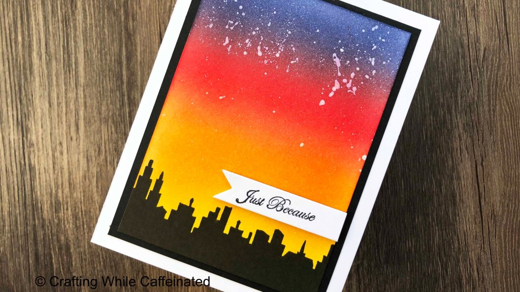 A Just Because Handmade Greeting Card with a silhouette city scape. The ink blended background is based on a sunset with a few paint splattered stars at the top.