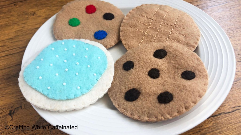 Four different cookies made from the free felt food pattern. The cookies I made with the pattern are chocolate chip, M&M, peanut butter and sugar cookie.